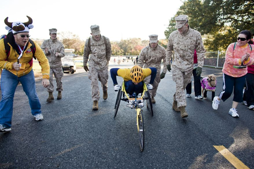 James Armstrong, at left, of Red Bank, N.J., and Miriam Camino-Wolosky, of Alexandria, Va., at right, join Marine Corps race volunteers in cheering on David Swope, of New Windsor, N.Y., as he climbs the final hill of the 36th Marine Corps Marathon in Arlington, Va. on Oct. 30, 2011.(T.J. Kirkpatrick/ The Washington Times)