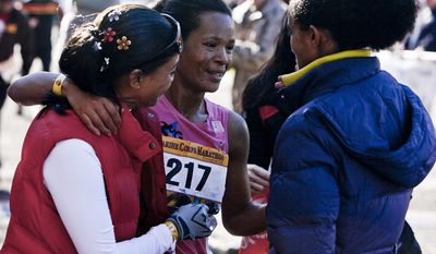 Tezata Dengersa, 30, of Turkey, greets family after crossing the finish line in 2:45:28 to win the women's division of the 36th Marine Corps Marathon in Arlington, Va. on Oct. 30, 2011.(T.J. Kirkpatrick/ The Washington Times)
