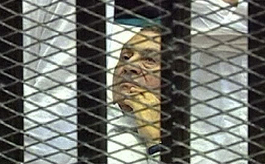 ** FILE ** Former Egyptian President Hosni Mubarak, 83, lies on a hospital bed inside the defendants' cage of a Cairo courtroom on Wednesday, Aug. 3, 2011, as his historic trial begins on charges of corruption and complicity in the killing of protesters during the uprising that ousted him. (AP Photo/Egyptian State Television, File)