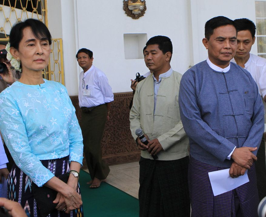 Aung San Suu Kyi (left), Myanmar's democracy icon, and Labor and Social Welfare Minister Aung Kyi (right) listen to questions from reporters during a press conference after their meeting at Seinleikanthar government guest house on Sunday, Oct. 30, 2011, in Yangon, Myanmar. (AP Photo/Khin Maung Win)