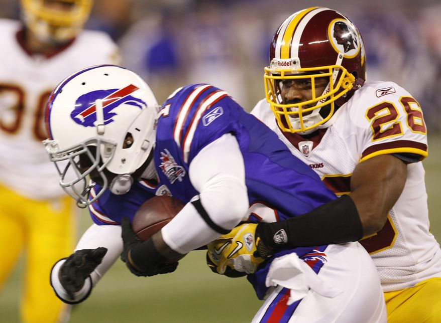 Buffalo Bills' Stevie Johnson, left, is wrapped up by Washington Redskins' Josh Wilson (28) during the first quarter of an NFL football game at the Rogers Centre in Toronto, Sunday, Oct. 30, 2011. (AP Photo/Derek Gee)