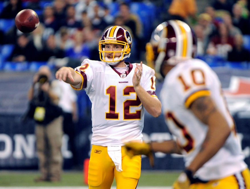 Washington Redskins quarterback John Beck (12) connects with teammate Jabar Gaffney (10) for a reception during the first half of an NFL football game in Toronto on Sunday, Oct. 30, 2011. (AP Photo/Gary Wiepert)