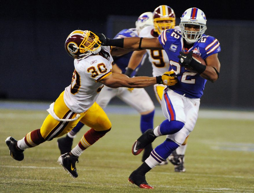 Buffalo Bills' Fred Jackson (22) runs under pressure from Washington Redskins' LaRon Landry (30) during the first half of an NFL football game at the Rogers Centre in Toronto, Sunday, Oct. 30, 2011. (AP Photo/Gary Wiepert)