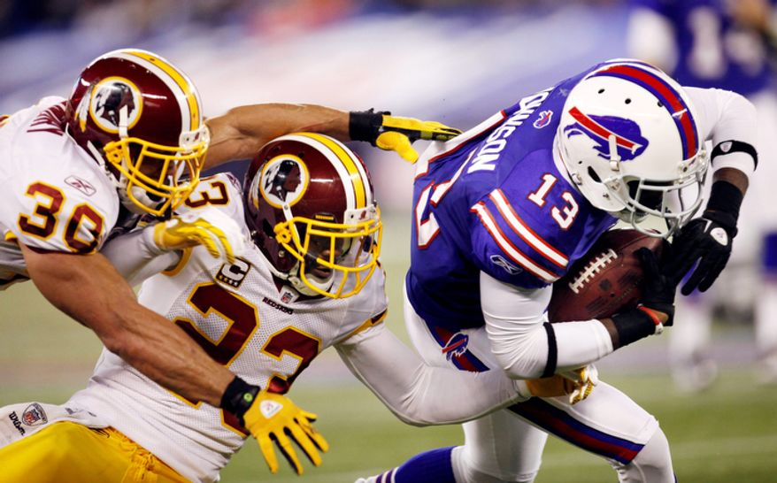 Buffalo Bills' Stevie Johnson (13) tries to get past Washington Redskins' LaRon Landry (30) and DeAngelo Hall (23)  during the first half of an NFL football game in Toronto on Sunday, Oct. 30, 2011. (AP Photo/Derek Gee)