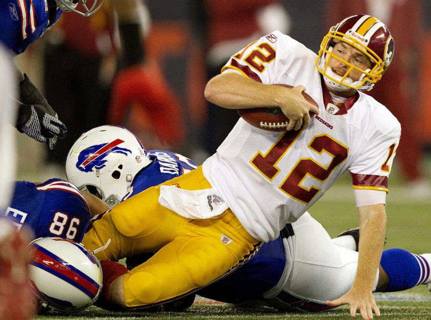 Buffalo Bills defensive ends Dwan Edwards (98) and Dareus Marcell, rear, sack Washington Redskins quarterback John Beck (12) during the second half of an NFL football game in Toronto on Sunday, Oct. 30, 2011. The Bills won 23-0. (AP Photo/The Canadian Press, Frank Gunn)