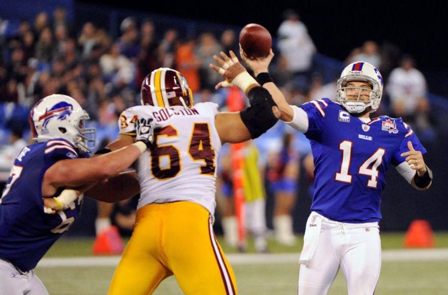 Buffalo Bills' Ryan Fitzpatrick (14) throws a touchdown pass to teammate Scott Chandler, not shown, under pressure from Washington Redskins' Kedric Golston (64) during the second half of an NFL football game in Toronto, Sunday, Oct. 30, 2011. The Bills won 23-0. (AP Photo/Gary Wiepert)