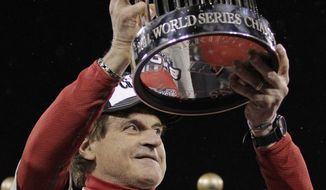 St. Louis Cardinals manager Tony La Russa holds up the Commissioner's Trophy after Game 7 of the World Series against the Texas Rangers on Friday, Oct. 28, 2011, in St. Louis. The Cardinals won 6-2 to win the series. (AP Photo/Charlie Riedel)