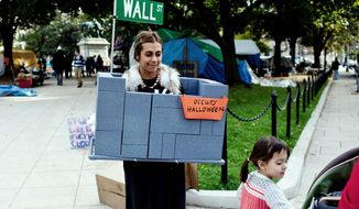 """Leeya Mehta, of Washington, with her daughter Mae, 3, wears what she called a """"timely costume"""" while walking along McPherson Square on Monday. But Occupy DC protesters, for the most part, kept focused on activism during the trick-or-treat day. (T.J. Kirkpatrick/The Washington Times)"""