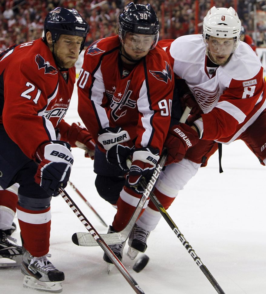 Washington Capitals centers Brooks Laich (21) and Marcus Johansson (90) battle Detroit Red Wings left wing Justin Abdelkader (right) for the puck during the third period of the Capitals' 7-1 home victory on Oct. 22, 2011. (Associated Press)