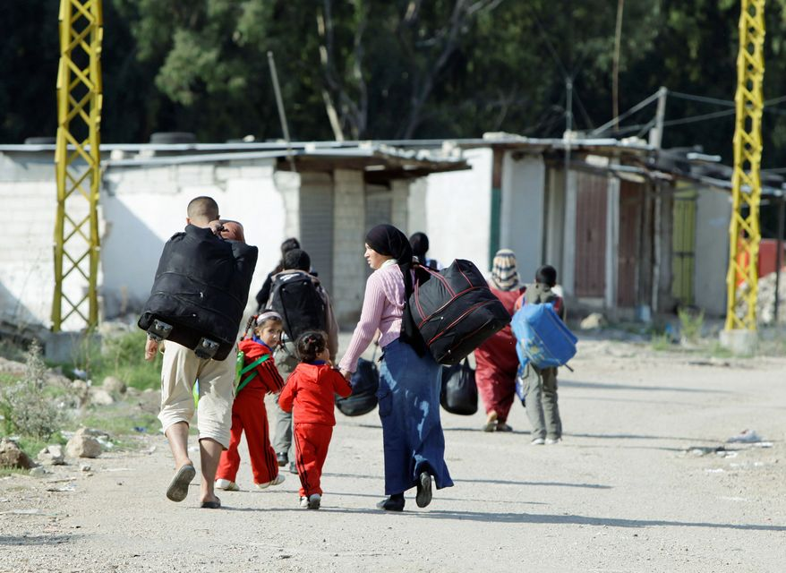 Syrians carry their belongings as they return to Syria from Arida in northern Lebanon on Monday. (Associated Press)