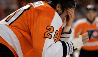 Philadelphia Flyers captain Chris Pronger puts his hand over his eyes as he heads for the locker room after being struck in the face with a stick during the first period of an NHL hockey game with the Toronto Maple Leafs, Monday, Oct. 24, 2011, in Philadelphia. (AP Photo/Tom Mihalek)