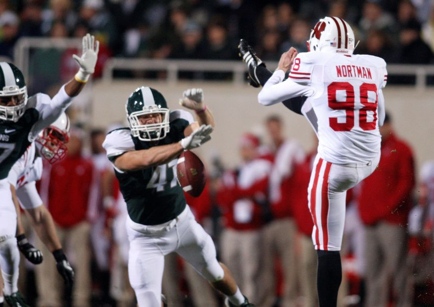 Michigan State's Kyler Elsworth (center) blocked a punt by Wisconsin's Brad Nortman, which was returned for a touchdown Oct. 22. The play proved pivotal in the Spartans' 37-31 victory. (Associated Press)