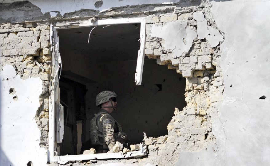 A U.S. soldier checks the damage at offices of the U.N.'s refugee agency, the UNHCR, caused by a suicide bomber in Kandahar, Afghanistan, on Oct. 31, 2011. The attack killed four people and severely damaged the U.N. agency's building, Afghan officials said. (Associated Press)