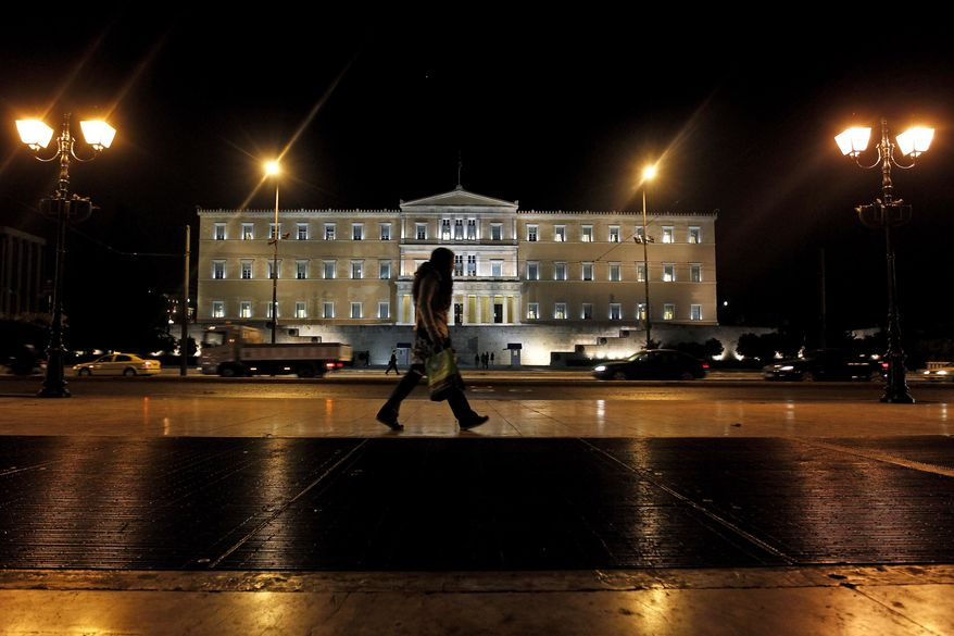 A woman walks outside the Greek parliament in central Athens, on Nov. 1, 2011. Lawmakers in Greece's ruling Socialist party revolted over their prime minister's surprise decision to hold a referendum on a European debt deal, threatening the very survival of his embattled government. (Associated Press)