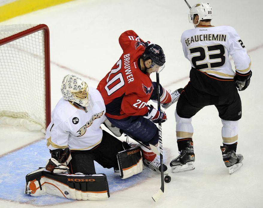 Washington Capitals left wing Troy Brouwer (20) battles for the puck in front of the net against Anaheim Ducks goalie Jonas Hiller (1), of Switzerland, and Francois Beauchemin (23) during the first period of an NHL hockey game Tuesday, Nov. 1, 2011, in Washington. (AP Photo/Nick Wass)