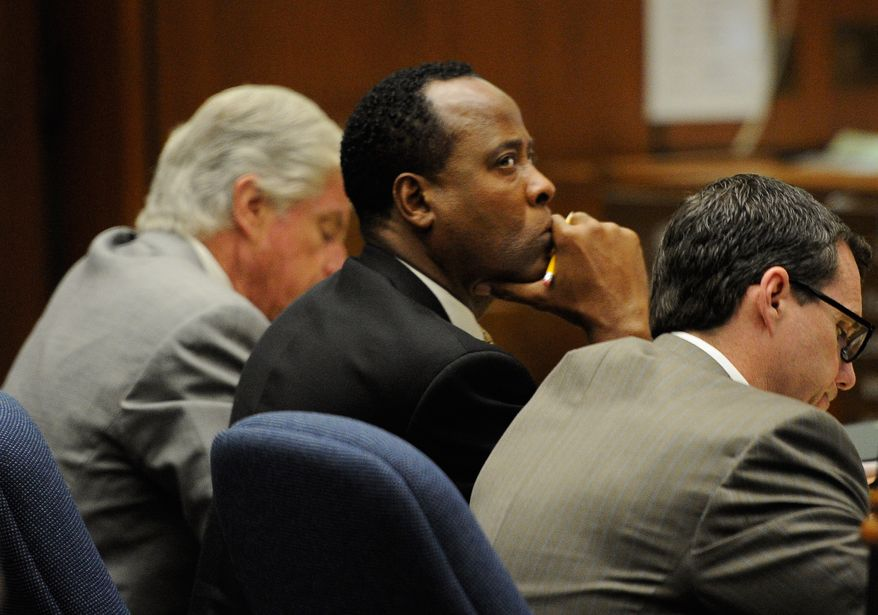 Dr. Conrad Murray (center), flanked by defense lawyers J. Michael Flanagan (left) and Ed Chernoff, listens during the final stages of the defense during his involuntary manslaughter trial in the death of singer Michael Jackson in the Los Angeles Superior Court on Monday, Oct. 31, 2011. (AP Photo/Kevork Djansezian, Pool)