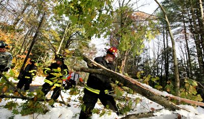 Army National Guard Sgt. Danny Sousa (center) and others from the 79th Troop Command work alongside  firefighters to clear trees and make roads passable in Barre, Mass., on Monday, Oct. 31, 2011. (AP Photo/Elise Amendola)