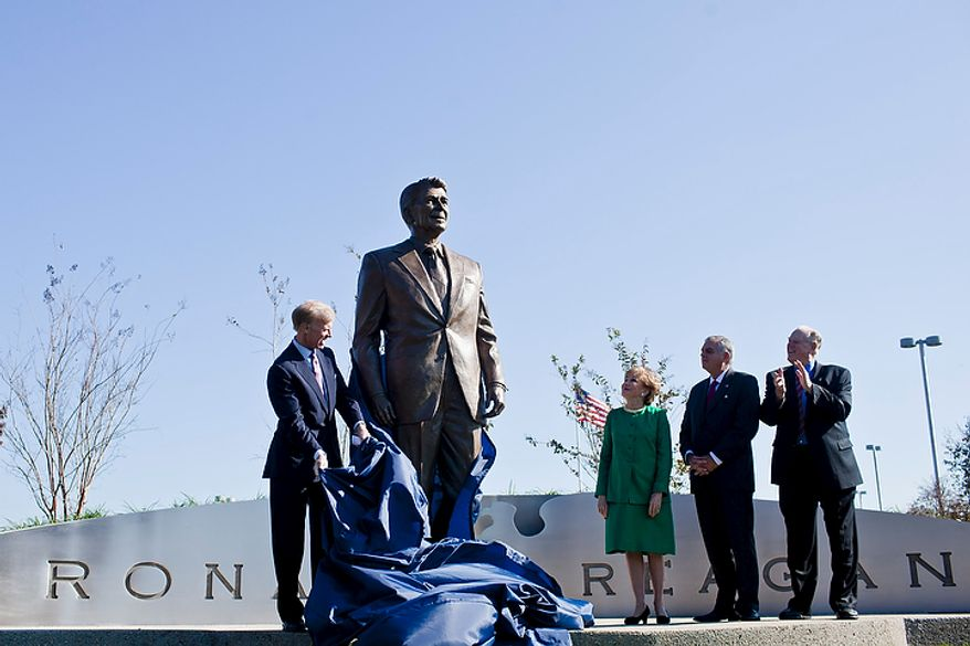 Frederick Ryan Jr. (left), chairman of the board of trustees of the Ronald Reagan Presidential Foundation, unveils a bronze statue of Ronald Reagan at Reagan National Airport in Arlington, Va., on Nov. 1, 2011. The statue was unveiled as part of a dedication ceremony on the centennial of the former president's birth. Also attending the event were former Transportation Secretary Elizabeth Dole (second from left); Charles Snelling (second from right), chairman of the board of the Metropolitan Washington Airports Authority; and Transportation Secretary Ray LaHood. (T.J. Kirkpatrick/The Washington Times)