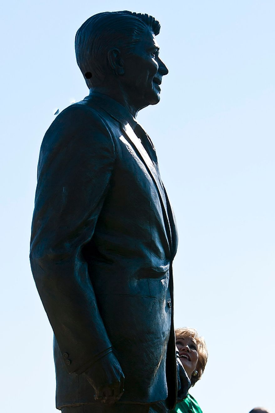 Former Transportation Secretary Elizabeth Dole looks up at a bronze statue of Ronald Reagan at Reagan National Airport in Arlington, Va., on Nov. 1, 2011. The statue was unveiled as part of a dedication ceremony on the centennial of the former president's birth. (T.J. Kirkpatrick/The Washington Times)