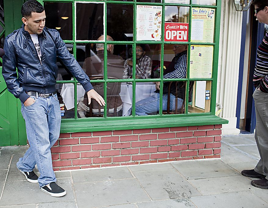 Frank Ramirez, a manager at Don Lobo's Mexican Grill, describes the scene where a young man was shot in the head from a passing car on Halloween night in front of the restaurant in the 2800 block of M St. NW in Georgetown, seen in Washington, D.C. on Nov. 1, 2011. (T.J. Kirkpatrick/ The Washington Times)