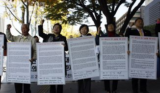 South Korean protesters shout slogans near the U.S. Embassy in Seoul on Tuesday, Nov. 1, 2011, as they hold petitions at a rally denouncing the crimes of U.S. soldiers. (AP Photo/Lee Jin-man)