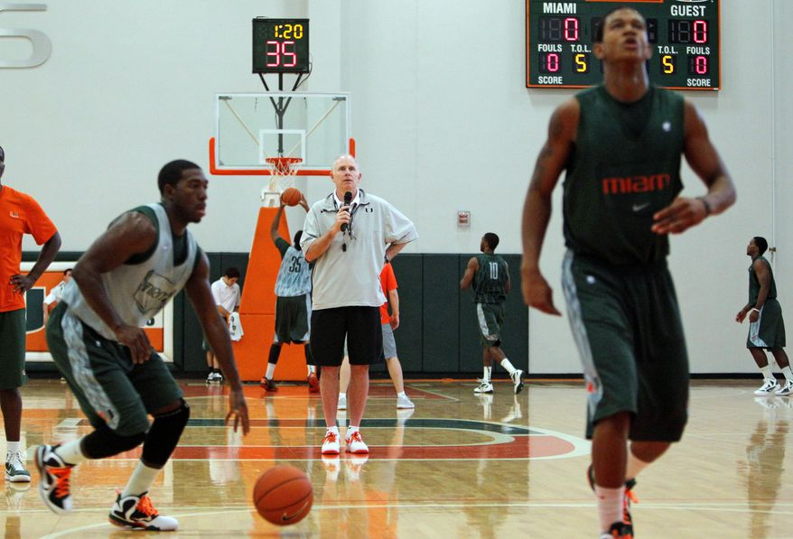 In this photo taken Oct. 16, 2011, Miami head coach Jim Larranaga, center, watches his players during NCAA college basketball practice in Coral Gables, Fla. (AP Photo/Lynne Sladky)