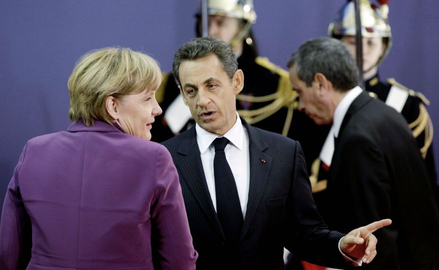 French President Nicolas Sarkozy (center) speaks with German Chancellor Angela Merkel during arrivals for the G-20 economic summit in Cannes, France, on Wednesday. (Associated Press)