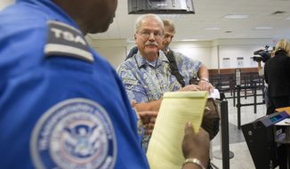 **FILE** Airline passenger Don Heim (right) of Alpharetta, Ga., is briefed by Transportation Security Administration trainer Byron Gibson before going through a new expedited security line on Oct. 4, 2011, at Hartsfield-Jackson International Airport in Atlanta. (Associated Press)