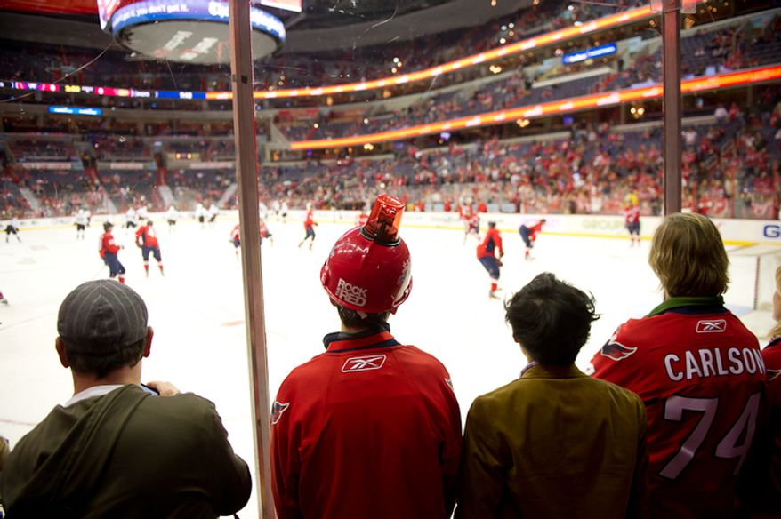 Capitals fan Chris Voegle, second from left, wears a hat with a goal light as he watches the Washington Capitals warm up before taking on the Anaheim Ducks in NHL Hockey at the Verizon Center, Washington, DC, Tuesday, November 1,  2011. (Andrew Harnik / The Washington Times)