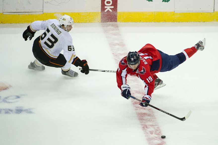 Nicklas Backstrom (19) of the Washington Capitals falls while passing against the Anaheim Ducks in NHL Hockey at the Verizon Center, Washington, DC, Tuesday, November 1,  2011. At left is Nick Bonino (63) of the Anaheim Ducks. (Andrew Harnik / The Washington Times)