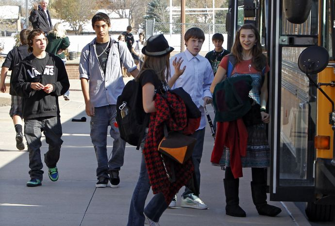 Students at Carmody Middle School in Lakewood, Colo., head for waiting buses after school on Oct. 28, 2011. (Associated Press)