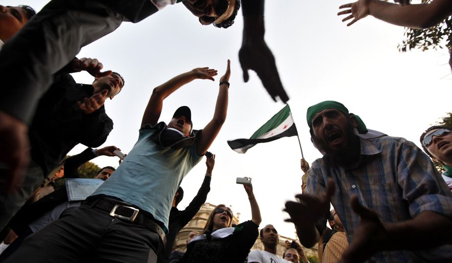 Protesters chant slogans during a demonstration against the Syrian regime in front of the Arab League headquarters in Cairo on Wednesday, Nov. 2, 2011. (AP Photo/Khalil Hamra)