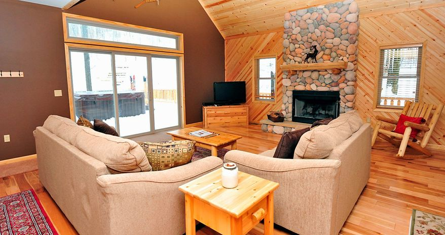 The great room has a floor-to-ceiling fireplace and a glass door that looks out onto the deck and oversized hot tub. All of the home's furnishings convey to the new owner.