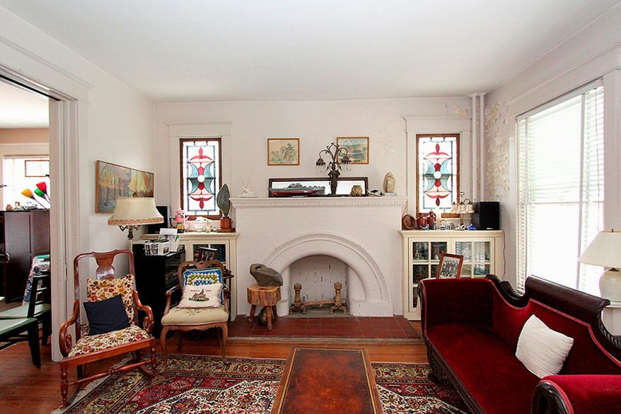 The living room's wood-burning fireplace is flanked by glass-front cabinets and stained-glass windows.