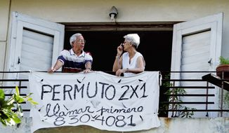 "The sign below Ives Lopez and his wife Nilda Bouzo in Havana reads ""Exchange Apartment Two for One."" Property exchanges were already legal and now so are sales. (Associated Press)"