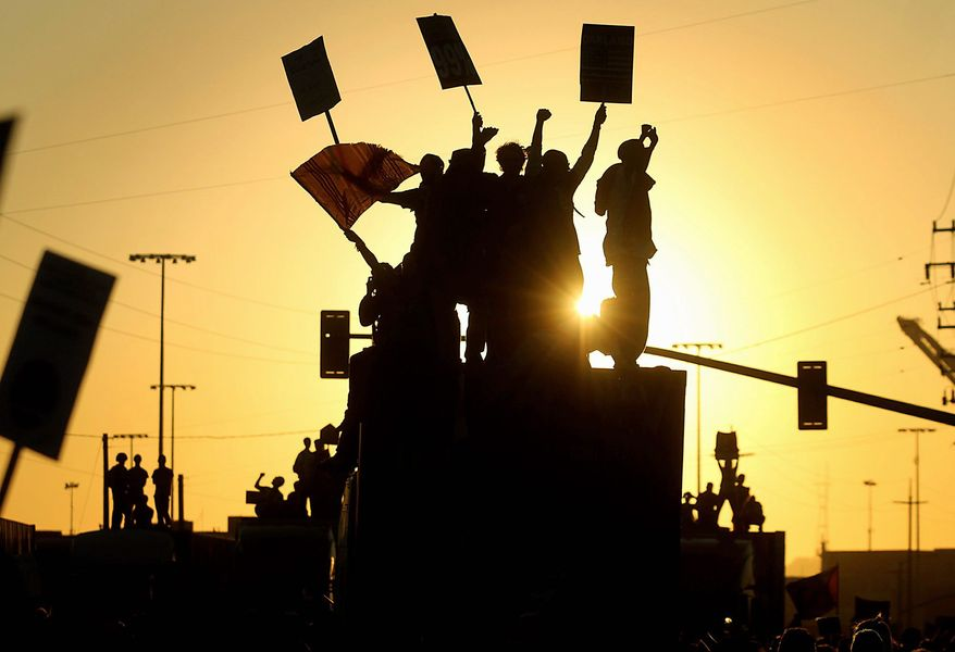 Occupy Oakland protesters cheer as they take over tractor-trailers loaded with shipping containers at the Port of Oakland on Wednesday, effectively shutting down the United States' fifth-busiest port during a day of nonstop protesting in the California city. (Associated Press)