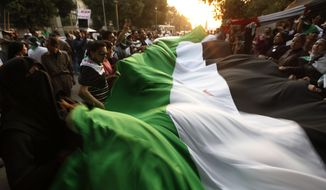 Protesters wave a large Syrian flag during a demonstration against the regime of Syrian President Bashar Assad in front of the Arab League headquarters in Cairo on Wednesday, Nov. 2, 2011. (AP Photo/Khalil Hamra)