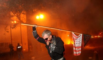 """Occupy Oakland"" protester Mike Clift runs from tear gas on Thursday, Nov. 3, 2011, in Oakland, Calif. Following a mainly peaceful day-long protest by thousands of anti-Wall Street demonstrators, several hundred rallied through the night, with some painting graffiti, breaking windows and setting file to garbage cans. (AP Photo/Noah Berger)"