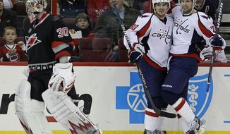 Washington Capitals' Marcus Johansson and Troy Brouwer celebrate Brouwer's goal against Carolina Hurricanes goalie Cam Ward during the second period in Raleigh, N.C., Friday, Nov. 4, 2011. Washington won 5-1. (AP Photo/Gerry Broome)