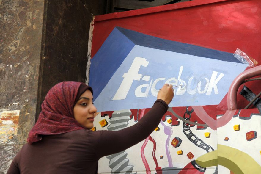 ** FILE ** In this March 30, 2011, file photo. an art student from the University of Helwan paints the Facebook logo on a mural commemorating the revolution that overthrew Hosni Mubarak in the Zamalek neighborhood of Cairo, Egypt. (AP Photo/Manoocher Deghati, File)