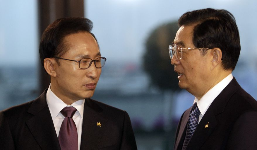 South Korean President Lee Myung-bak (left) speaks with Chinese President Hu Jintao during a roundtable meeting at a G-20 summit in Cannes, France on Nov. 4, 2011. (Associated Press)