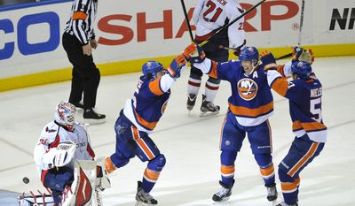 Washington Capitals goalie Tomas Vokoun reacts as New York Islanders' P.A. Parenteau, Brian Rolston  and Frans Nielsen celebrate what ended up being the game-winning goal by Parenteau. The Isles would add an empty-netter and won 5-3. (AP Photo/Kathy Kmonicek)
