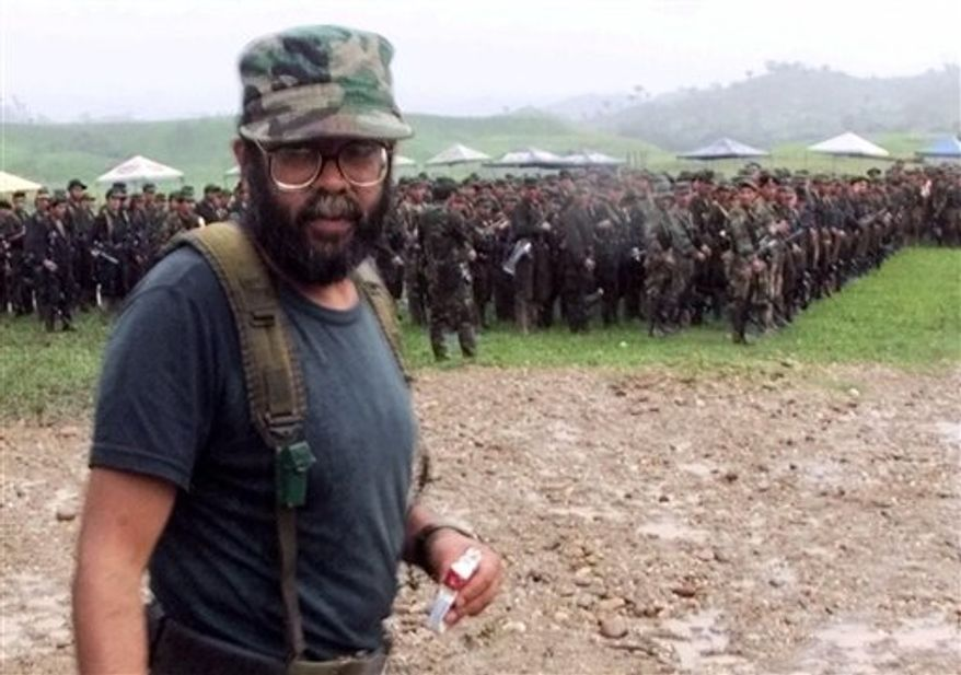FILE - In this April 28, 2000 file photo, Alfonso Cano, a Revolutionary Armed Forces of Colombia (FARC) commander who will head the Boliviarian Movement, a new clandestine political party for the rebels, attends a practice ceremony for the political party opening outside of San Vicente del Caguan in the FARC controlled zone of Colombia. According to Colombian military authorities, Cano, the top FARC commander, was killed in a military operation on Friday Nov. 4, 2011. (AP Photo/Scott Dalton, File)