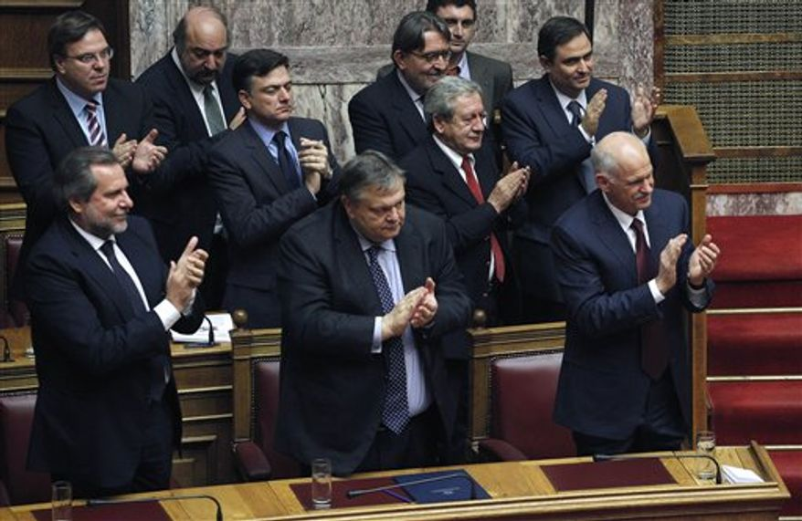Greek Prime Minister George Papandreou, bottom right, minister of Finance Evangelos Venizelos, bottom left, and other lawmakers clap hands after the announcement of the confidence vote meeting at the parliament in Athens, early Saturday, Nov. 5, 2011.Greece's prime minister has survived a confidence vote in parliament, calming a revolt in his Socialist party with a pledge to seek an interim government that would secure a vital new European debt deal.(AP Photo/Petros Giannakouris)