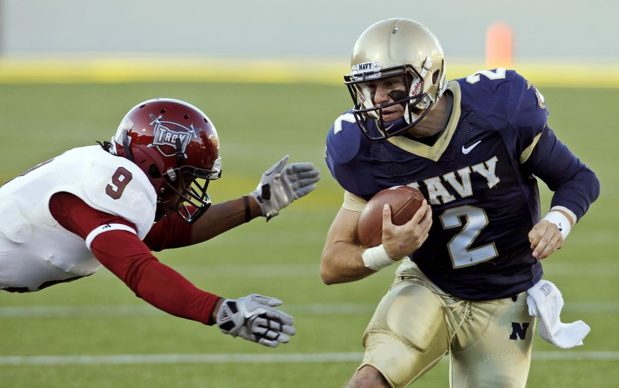 Navy quarterback Kriss Proctor (2) evades Troy defensive back LaDarrius Madden (9) on a short gain during the second quarter of an NCAA college football game Saturday, Nov. 5, 2011, in Annapolis, Md. (AP Photo/Ann Heisenfelt)