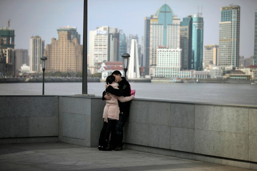"A man and woman kiss at the riverfront promenade called ""the Bund,"" one of the most popular tourist spots in Shanghai, an economic hub for China's changing economy. (Associated Press)"