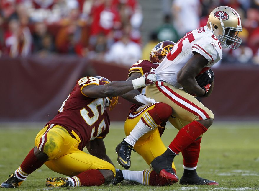 San Francisco 49ers tight end Vernon Davis tries to rush past Washington Redskins defenders London Fletcher and DeAngelo Hall in the second half in Landover, Md., Sunday, Nov. 6, 2011. (AP Photo/Pablo Martinez Monsivais)