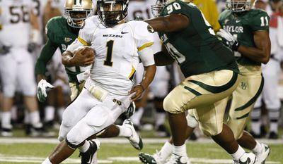 Missouri quarterback James Franklin (1) runs past Baylor's Nicolas Jean-Baptiste (right) during an NCAA football game on Saturday, Nov. 5, 2011, in Waco, Texas. Baylor won 42-39. (AP Photo/The Waco Tribune-Herald, Jose Yau)