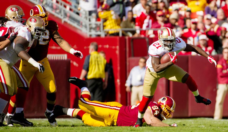 Washington Redskins Adam Carriker (94) can't stop San Francisco 49ers Frank Gore (21) from picking up 14 yards during the first quarter. (Andrew Harnik / The Washington Times)