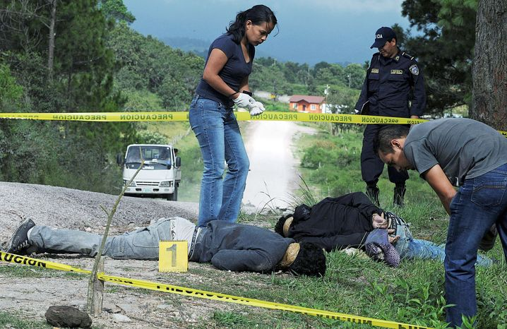 A police forensic team examines the bodies of three people said to be gang members and killed by unidentified assailants in the village of Los Hornos, Honduras. Honduras has become a main transit route for South American cocaine, a trend that has helped drive the country's homicide rate to the highest level in the world and left many villages dependent on the cocaine trade. (Associated Press)